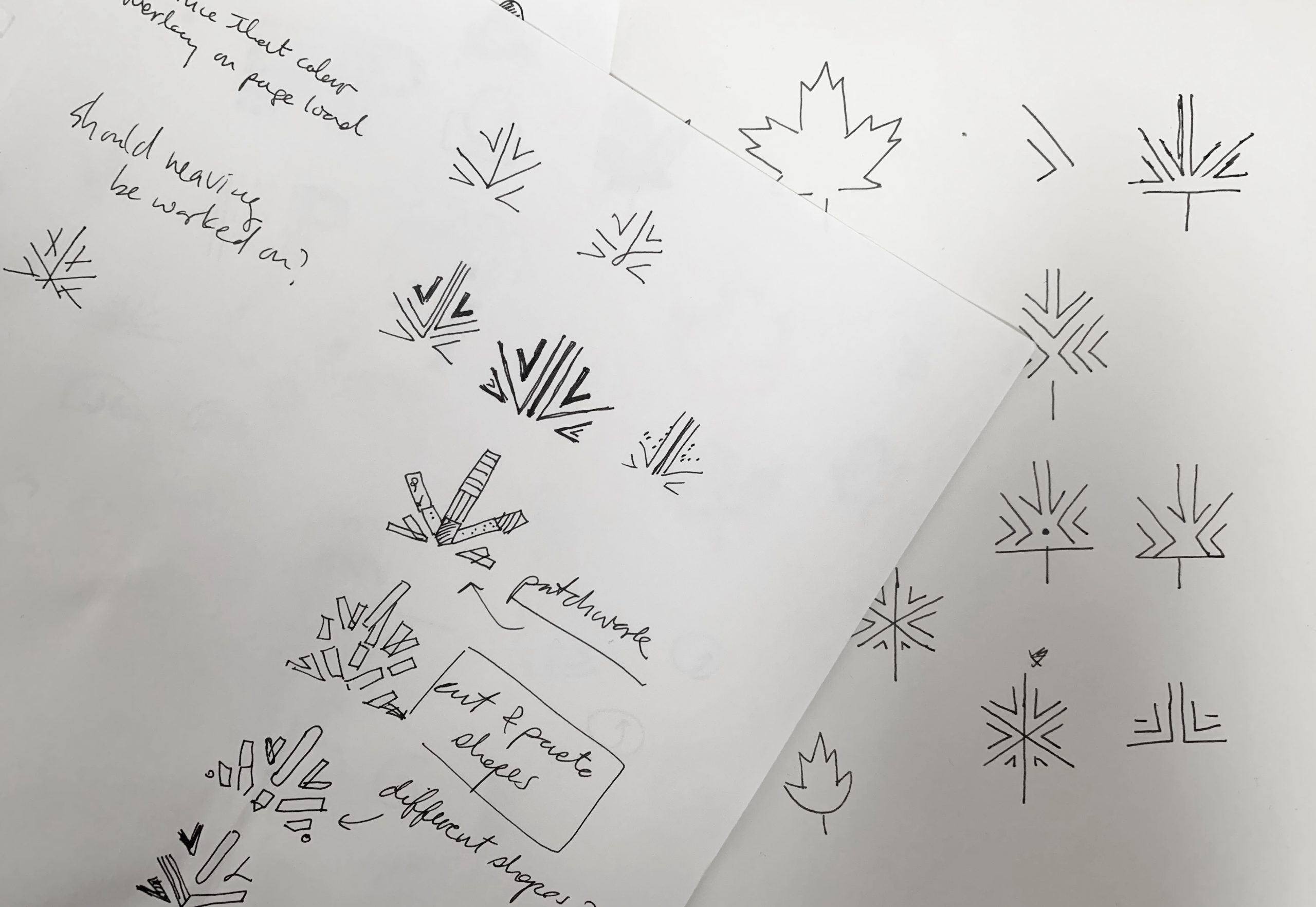 Two sketchbook pages showing a range of preliminary hand-drawn thumbnail sketches of the arrive logo in black fine line pen