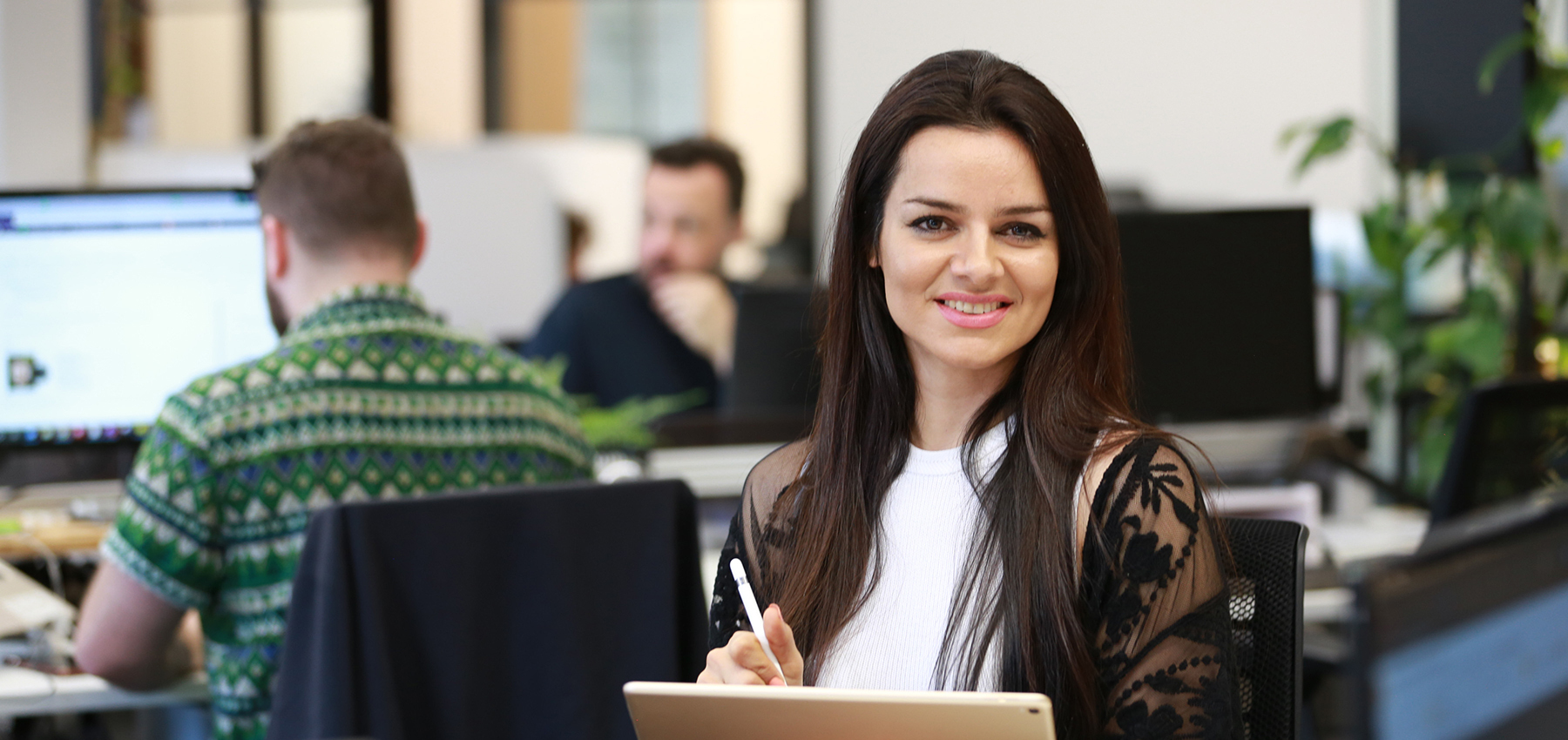 Maryam Sadeghi sits at a desk in the foreground of a busy tech office. she smiles confidently, holding a stylus in one hand and tablet in the other.