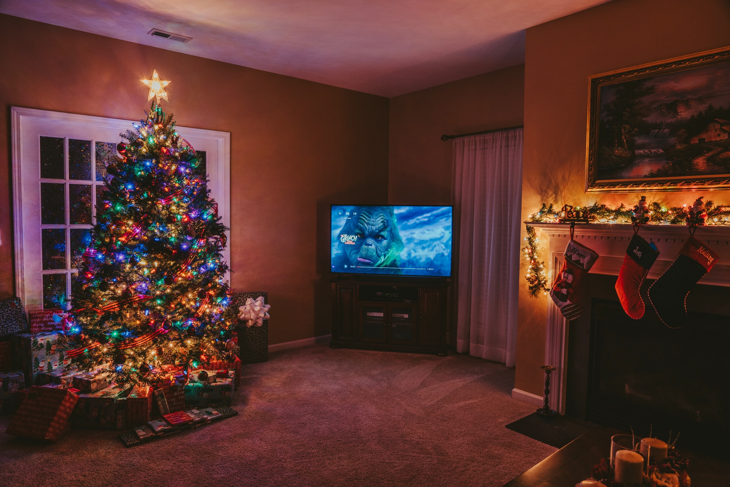 A decorated Christmas tree in a living room. Gifts are placed at the foot of the tree.