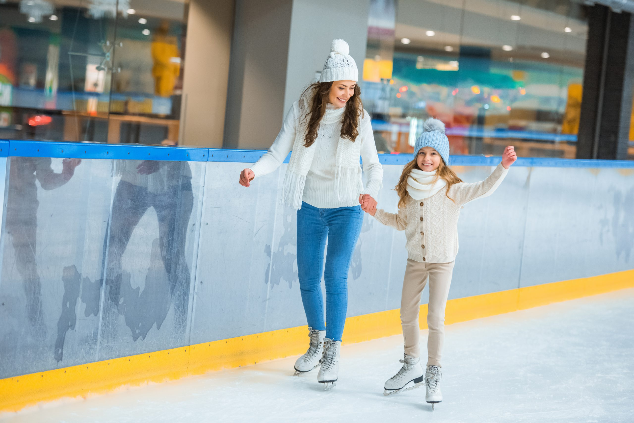 Mother and daughter skating on ice