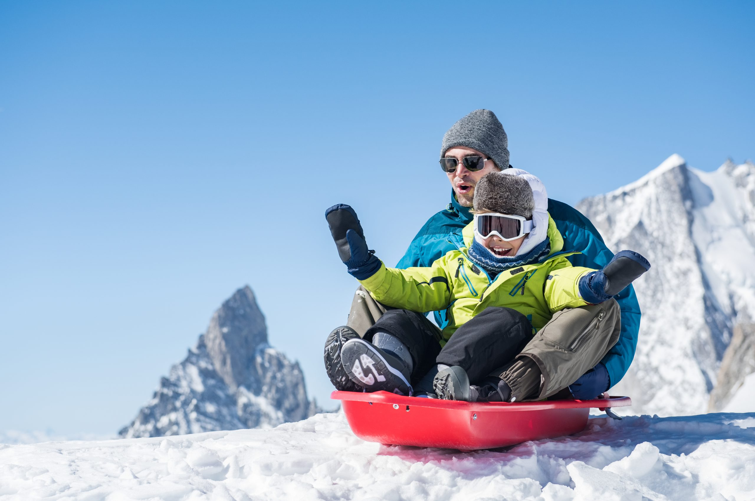 Father and son sledding or tobogganing