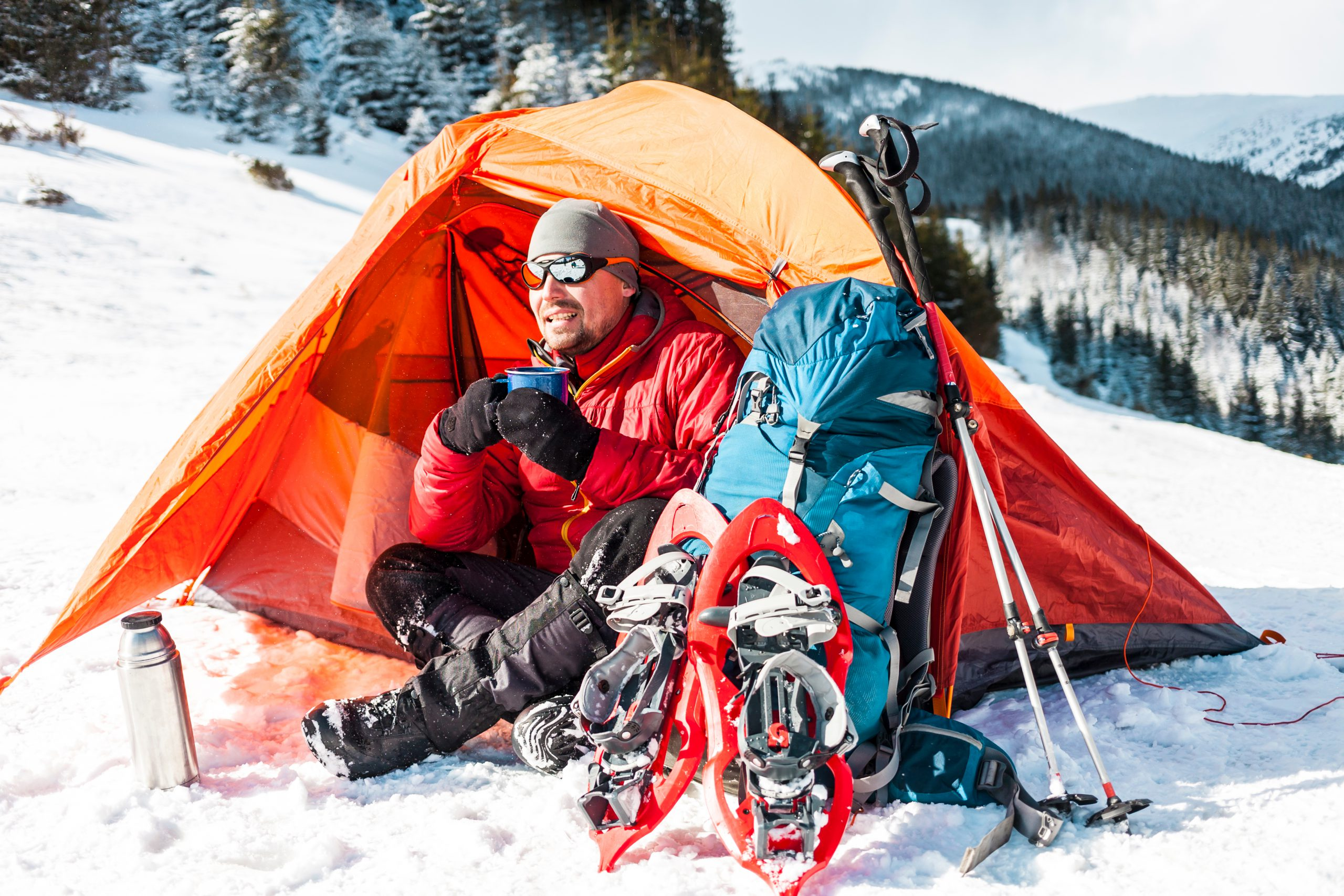 Man with winter camping equipment resting