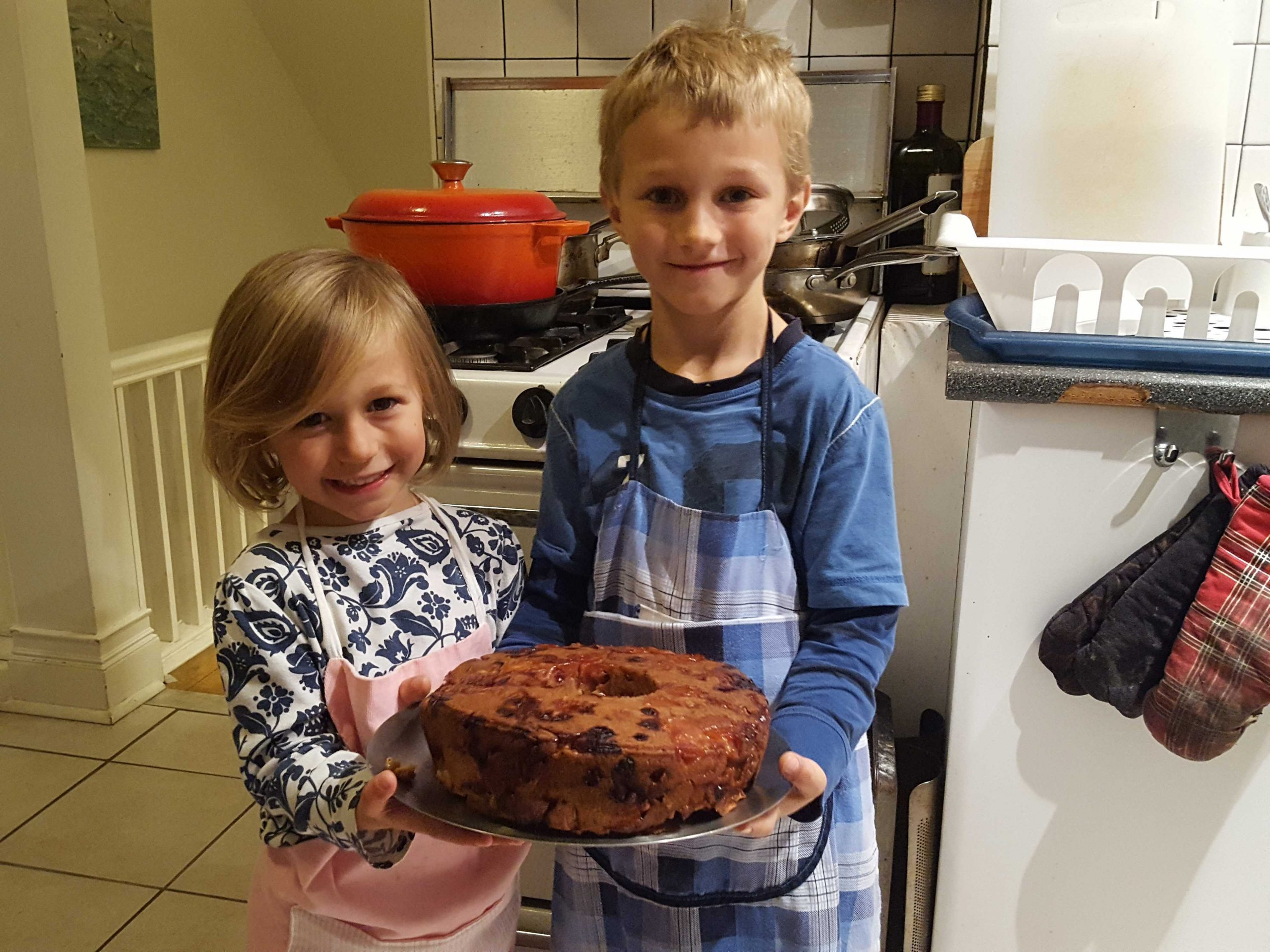 Kids holding a baked cake